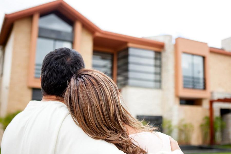 casal abraçado olhando para uma casa
