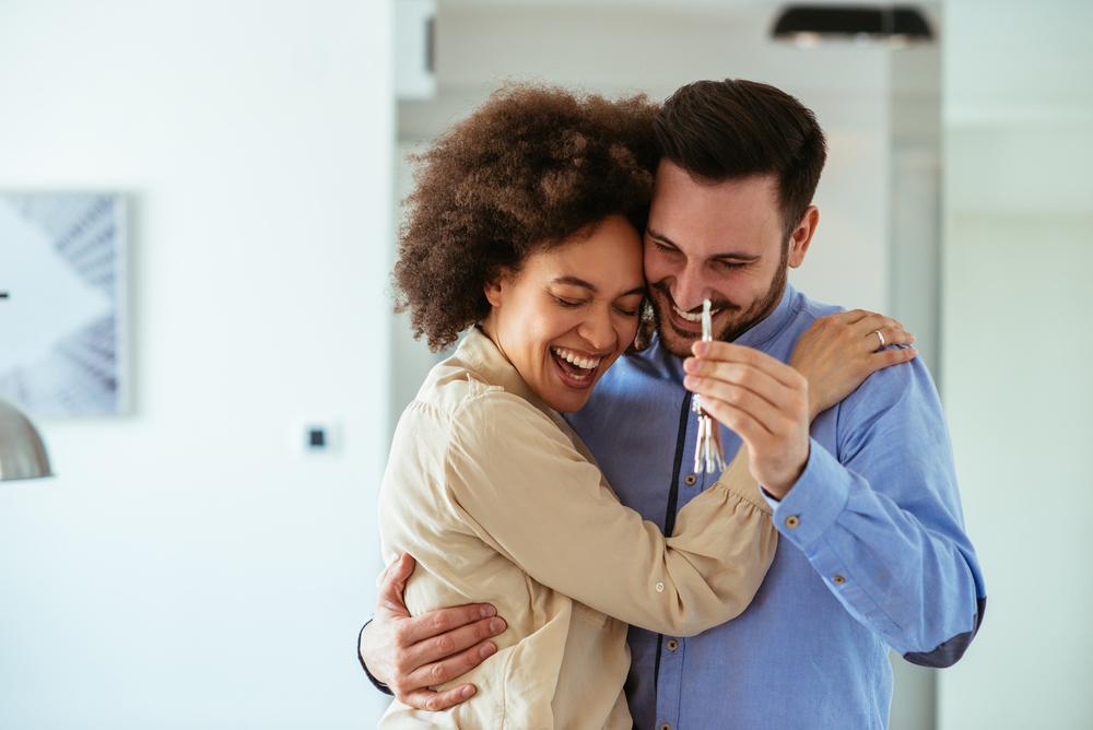 casal feliz se abraçando segurando molho de chaves